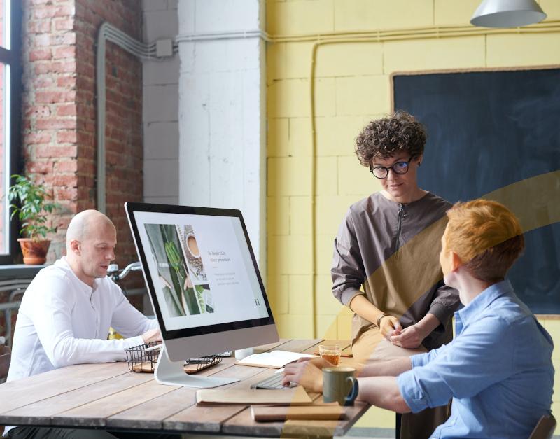 ERP-Software-Unser mobiles Hauptbild zeigt ein Mitarbeitergespräch vor einem Laptop im Unternehmen